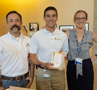 Drs. Bret McNabb and Jane Sykes present Gabe Gil (center) with his award.